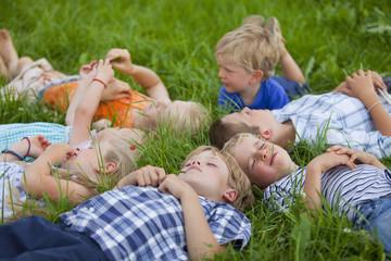 Deutschland, Bayern, Gruppe Kinder, die in der Wiese liegend