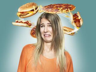 Angewidert junge Frau mit fliegenden Fast-Food um ihren Kopf, Composite