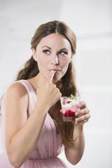 Deutschland, Junge Frau mit Glas Joghurt, Finger lecken