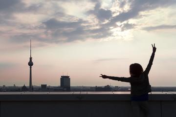 Deutschland, Berlin, junge Frau auf der Dachterrasse, Arme heben