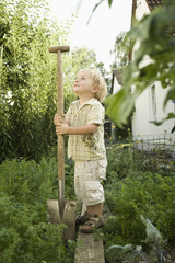 Deutschland, Bayern, Junge mit Schaufel im Garten