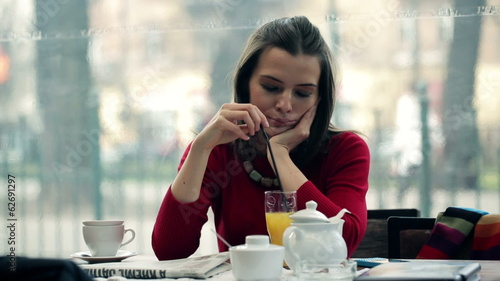 Sad, pensive woman drinking cocktail in cafe
