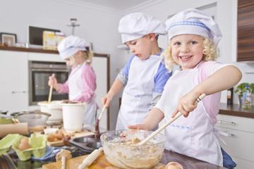 Deutschland, Mädchen und Jungen Vorbereitung Teig -und Backen cup cake in Küche