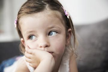 Traurig aussehende kleine Mädchen auf Sofa liegend