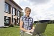 Deutschland, Nürnberg, Seniorin mit Laptop im Garten