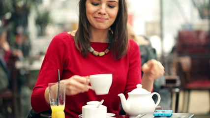 Happy woman pouring and drinking tea in crowded cafe