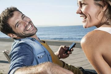 Spanien, Paar sitzt auf Bank mit Handy