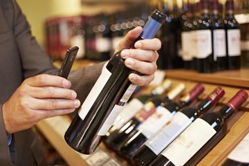 Deutschland, Köln, Mann, Foto machen Weinflasche im Supermarkt