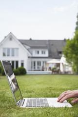 Deutschland, Köln, Mann mit Laptop im Garten