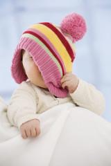 Baby verdeckt Gesicht mit Hut