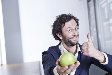 Deutschland, Köln Geschäftsmann mit grünen Apfel