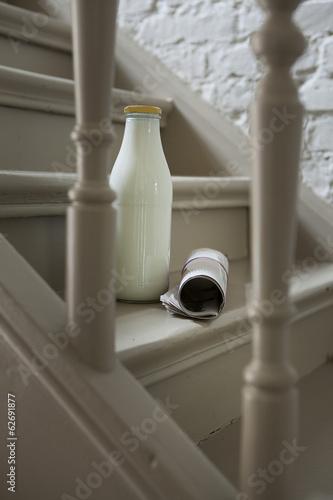 Milchflasche und Zeitung auf Treppe