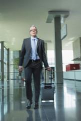 Deutschland, Stuttgart, Geschäftsmann ziehen Gepäck in Bürogebäude