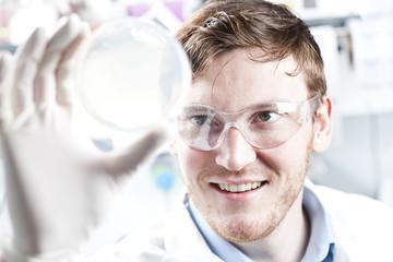 Deutschland, junger Wissenschaftler, prüfen Petrikolben