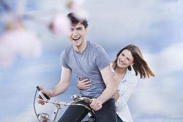 Deutschland, Köln, Junge Paare, die Spaß auf dem Fahrrad