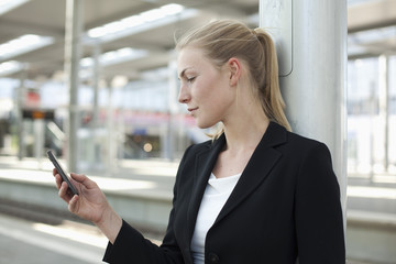 Deutschland, Düsseldorf, junge Frau mit Smartphone in der Station