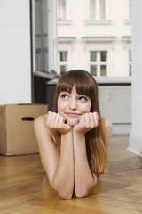 Deutschland, Berlin, junge Frau auf dem Boden liegend lächelnd