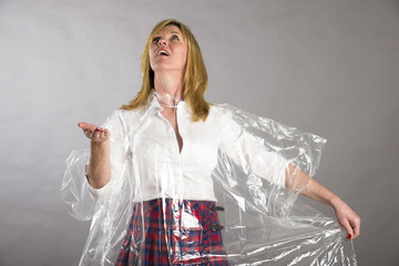 Woman wearing poncho checking for rain drops