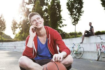 Junger Mann mit Smartphone- und Basketball