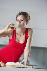 Deutschland, Junge Frau gießt Öl in Mehl