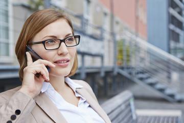 Deutschland, Köln, Geschäftsfrau sitzt auf der Bank, mit Telefon