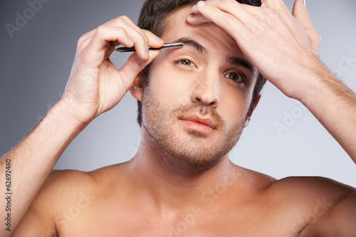 Man tweezing his eyebrows.