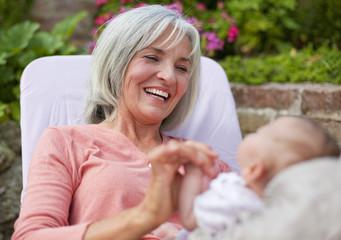 Deutschland, Bayern, Frau mit Enkel sitzen im Liegestuhl
