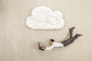 Geschäftsmann mit Laptop und unter Wolke Form Kissen fliegen