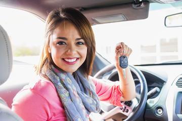 Lachendes Teenager-Mädchen in Auto hält Schlüssel