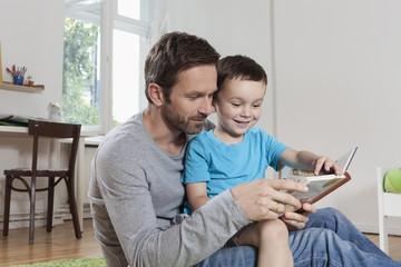 Deutschland, Berlin, Vater und Sohn lesen Buch