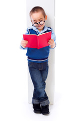 Little boy reading book near shelf