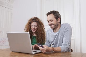 Deutschland, Berlin, Paar mit Laptop für Homeshopping