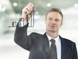 Geschäftsmann zeichnet Balkendiagramm auf Glas