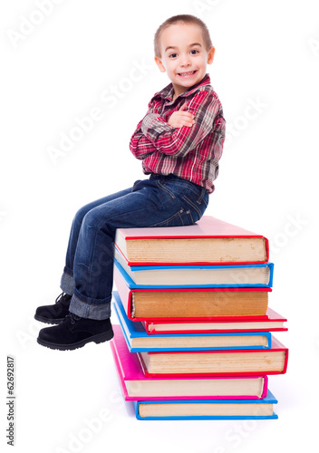 Little boy sitting on stacked colorful books