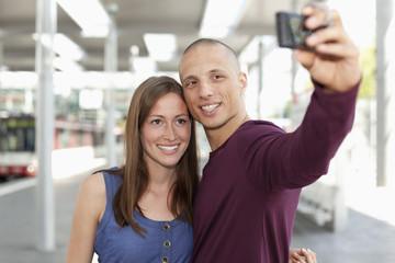 Deutschland, Düsseldorf, Junges Paar fotografiert sich selbst mit Smartphone