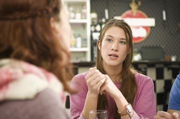 Deutschland, München, Junge Freunde im Café diskutieren