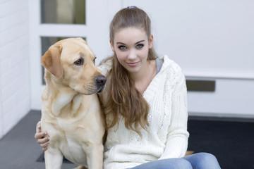 Teenager-Mädchen mit Hund sitzt vor einer Eingangstür