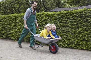 Deutschland, Köln, Vater mit Sohn in der Schubkarre