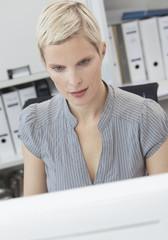 Geschäftsfrau arbeiten am Computer, Aktenordner im Hintergrund