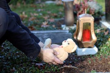 Angehöriger legt Teddy auf Grab von Verstorbenen