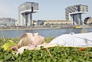 Deutschland, Köln, Junge Frau liegt entspannt im Gras