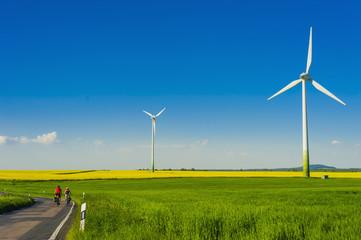 Deutschland, Sachsen, Windkraftanlagen in Rapsfeld