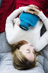 Deutschland, München, Junge Frau schläft auf der Couch mit Wärmflasche