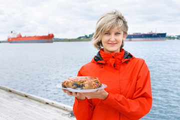 Happy woman holding cooked crab on plate