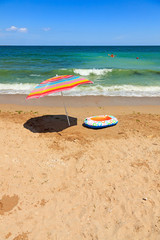 Beach umbrella and toy boat at sea