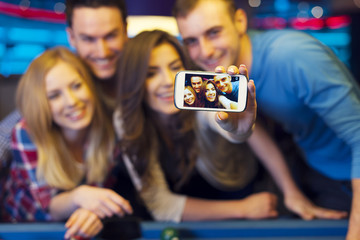 Smiling friends taking selfie photo from nightclub with billiard