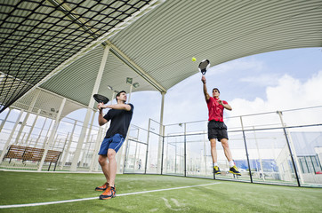 Paddle tennis players in wide angle ready for shot