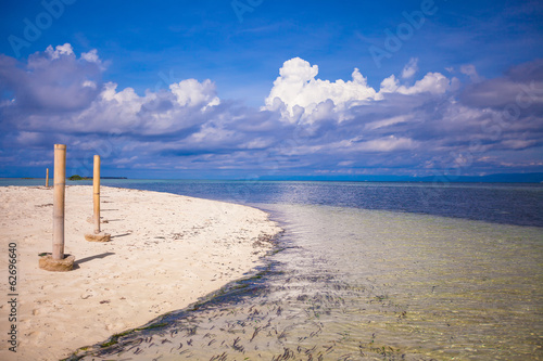 Perfect white beach with turquoise water and a small fence on a