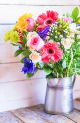 Colorful bouquet of spring flowers in vintage vase on rustic woo