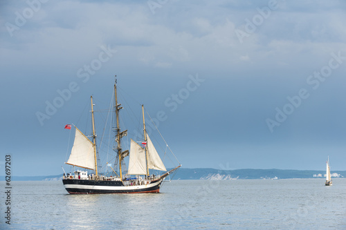 Tall ship on blue water against stormy clouds. Horizontal
